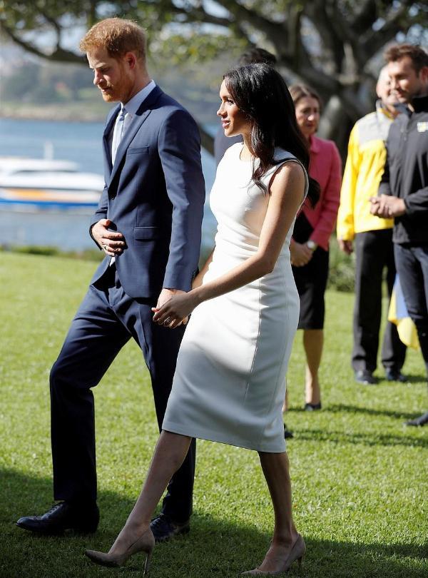 梅根王妃怀孕后穿贴身裙小腹微凸 获哈里王子牵手过草坪