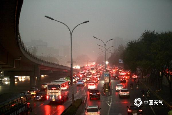 北京遭遇入冬后首场降雨 道路湿滑行人撑伞出行