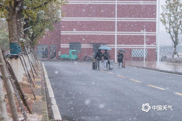 江西共青城市现明显降雪 学生顶风雪返乡